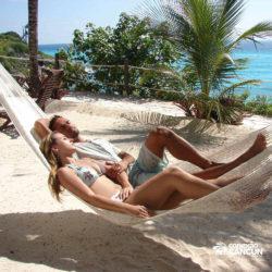 clube-de-praia-isla-discovery-catamara-dolphin-discovery-isla-mujeres-cancun-casal-relaxando-na-rede