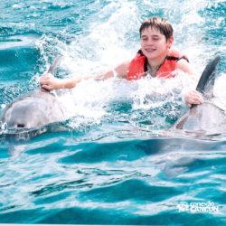 dolphin-royal-swim-vip-plus-isla-mujeres-cancun-menino-nadando-com-golfinho