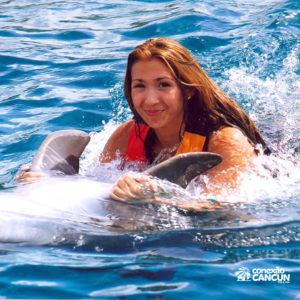 Mulher nada na barriga do golfinho